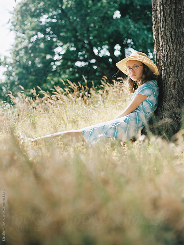 Girl looking towards the camera on a summer's day by Kirstin Mckee for Stocksy United