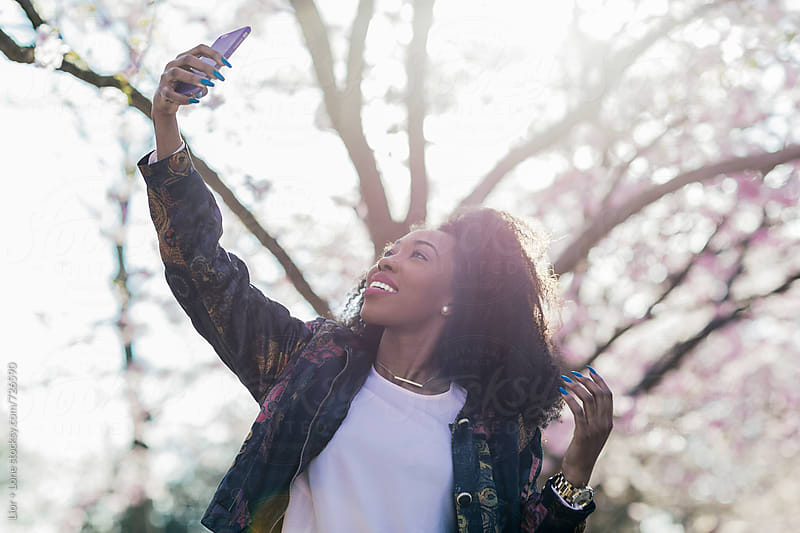 Young beautiful black woman taking a selfie in a park by Lior + Lone for Stocksy United