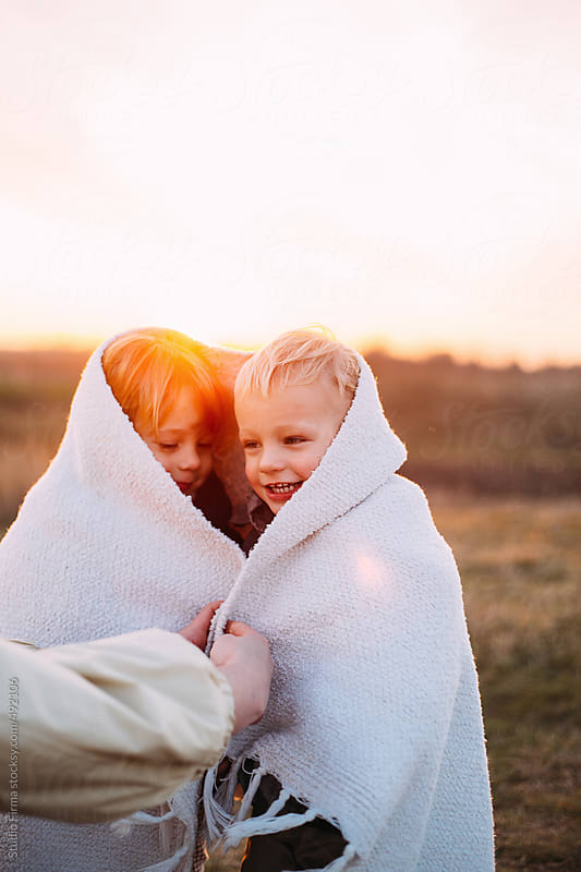 Mom covering her kids with white blanket. by Studio Firma for Stocksy United