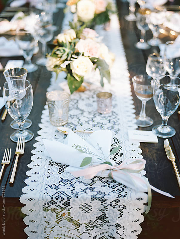 lace table runner and table set for gorgeous wedding on film by wendy laurel for Stocksy United