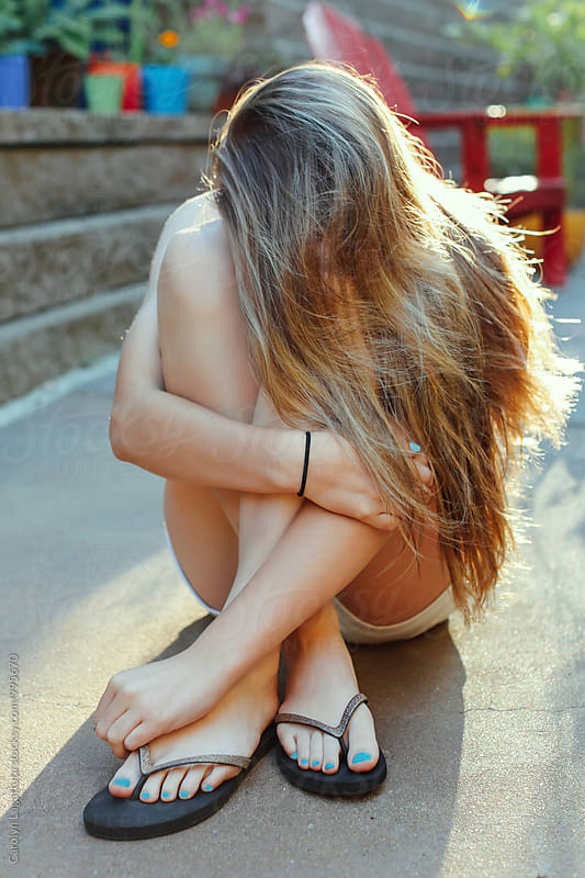 Teenage girl hiding behind her long, blonde hair by Carolyn Lagattuta for Stocksy United