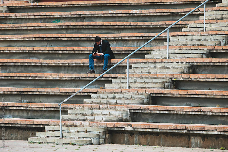 Young businesman sending text message with phone on street stairs. by BONNINSTUDIO for Stocksy United