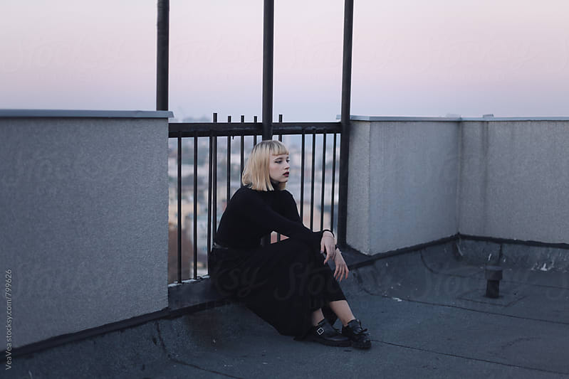 Stylish blonde woman on the roof of the building during sunset  by VeaVea for Stocksy United