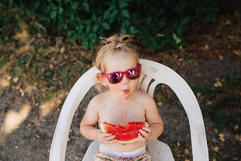 Cute toddler girl in sunglasses eating watermelon outside in the summer. by Jessica Byrum for Stocksy United