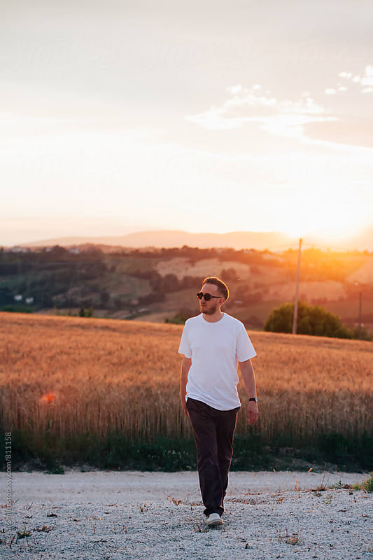 A man wearing sunglasses walks along a gravel path in the countryside at golden hour by Maresa Smith for Stocksy United
