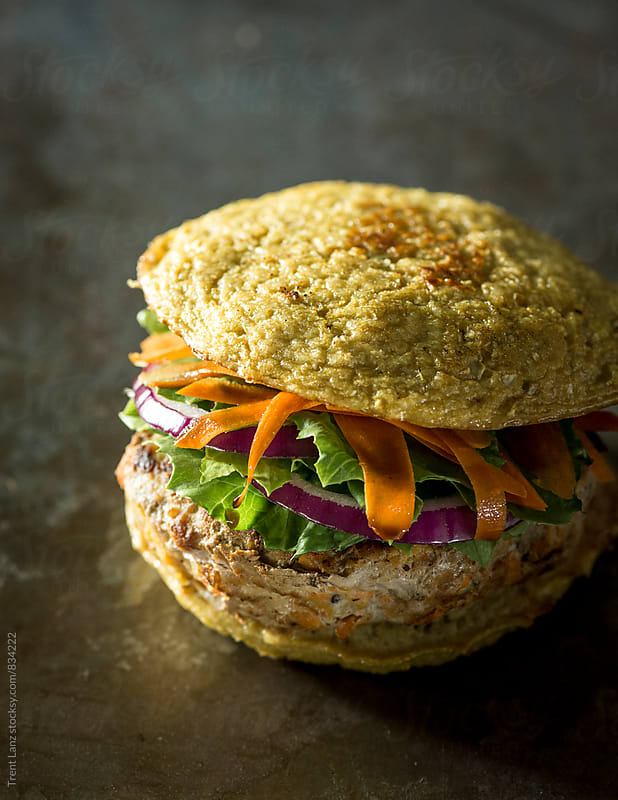 Paleo turkey burger with lettuce carrot and red onion by Trent Lanz for Stocksy United