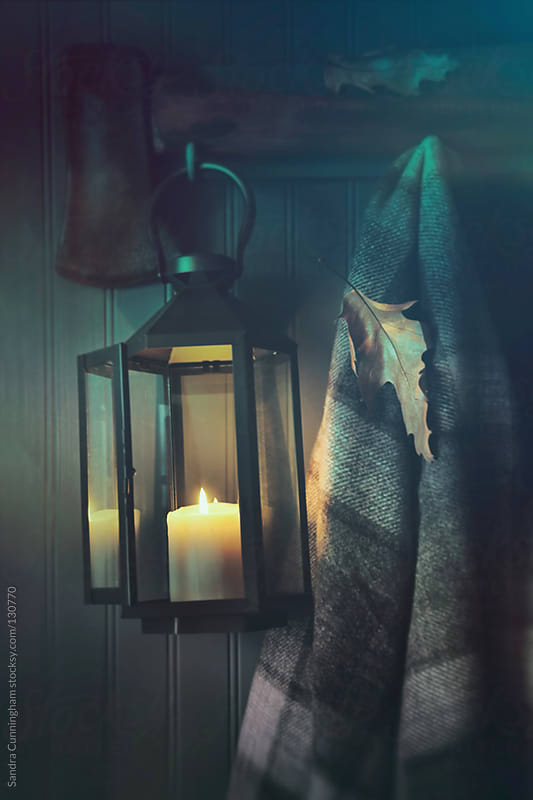 Lantern and blanket on coat hook by Sandra Cunningham for Stocksy United