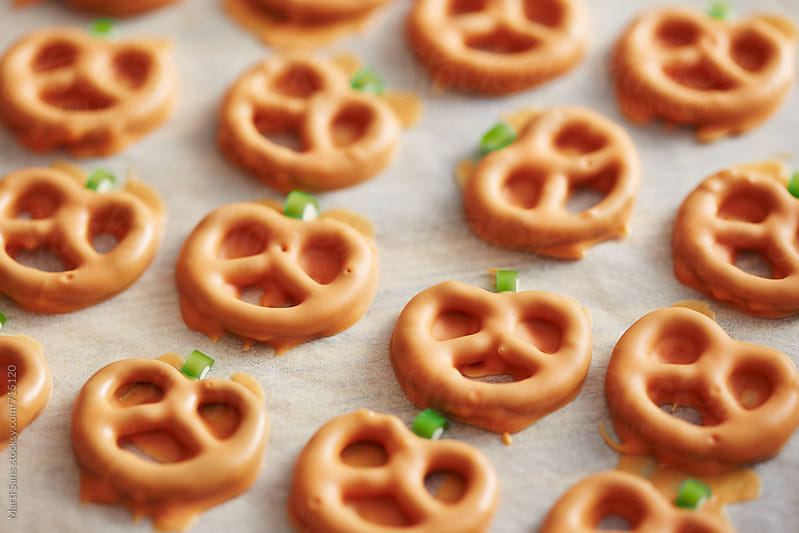 Preparing pumpkin shaped pretzels by Martí Sans for Stocksy United