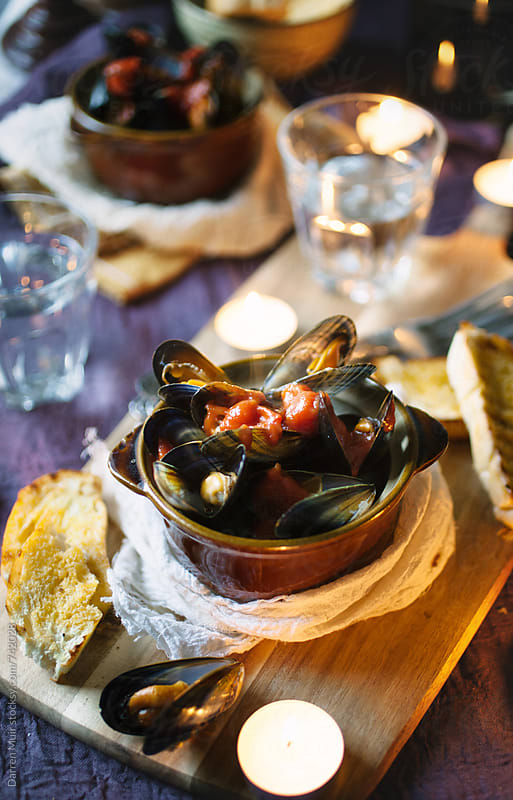 Mussels with tomato and garlic sauce,served with crusty bread. by Darren Muir for Stocksy United