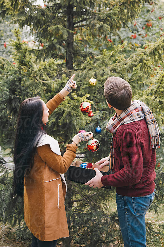 Couple decorating Christmas tree outdoors by T-REX & Flower for Stocksy United