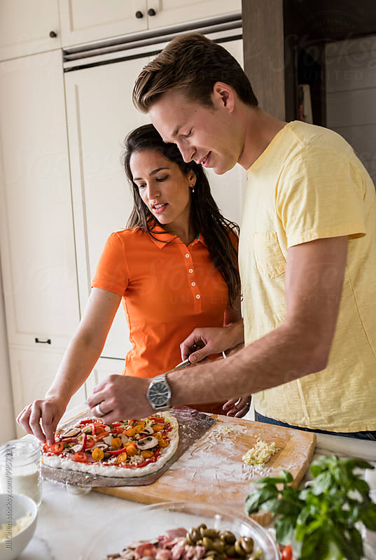 Couple Making Pizza in Kitchen by Jill Chen for Stocksy United
