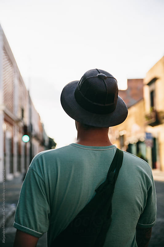 Back view of a man with a hat in the middle of the street between buildings by Alejandro Moreno de Carlos for Stocksy United