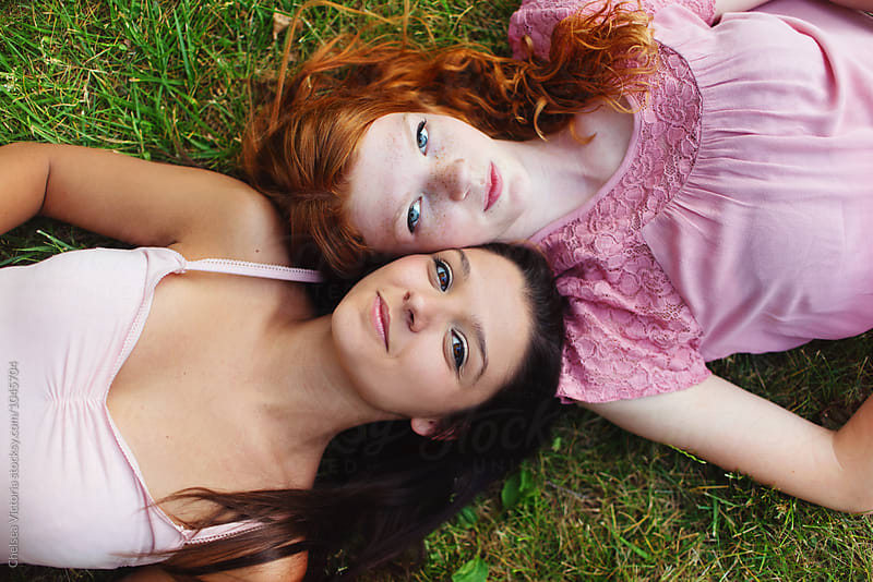 Two young friends laying in the grass by Chelsea Victoria for Stocksy United
