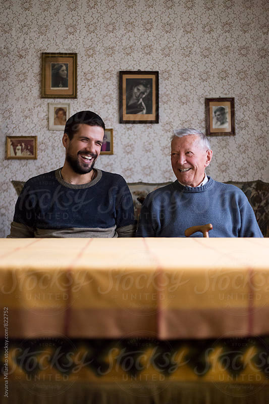 Grandpa and his kin laughing, sitting at the table in the living room  by Jovana Milanko for Stocksy United