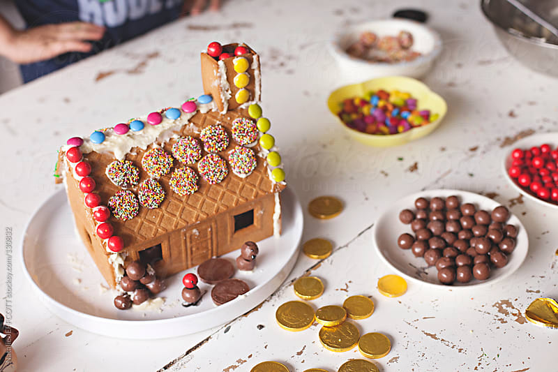 decorating a gingerbread house for Christmas by Natalie JEFFCOTT for Stocksy United