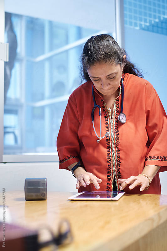 Female doctor at her office using tablet to take notes by Per Swantesson for Stocksy United
