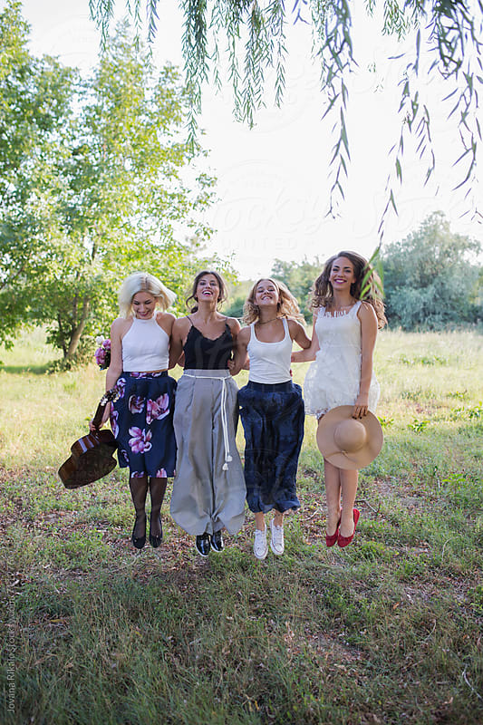 Happy female friends jumping in nature by Jovana Rikalo for Stocksy United