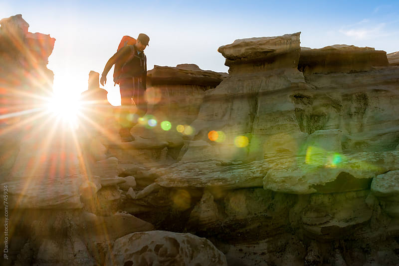 Backpacker Hiking over Hoodoos in Bisti Badlands Wilderness Area New Mexico at Sunrise by JP Danko for Stocksy United