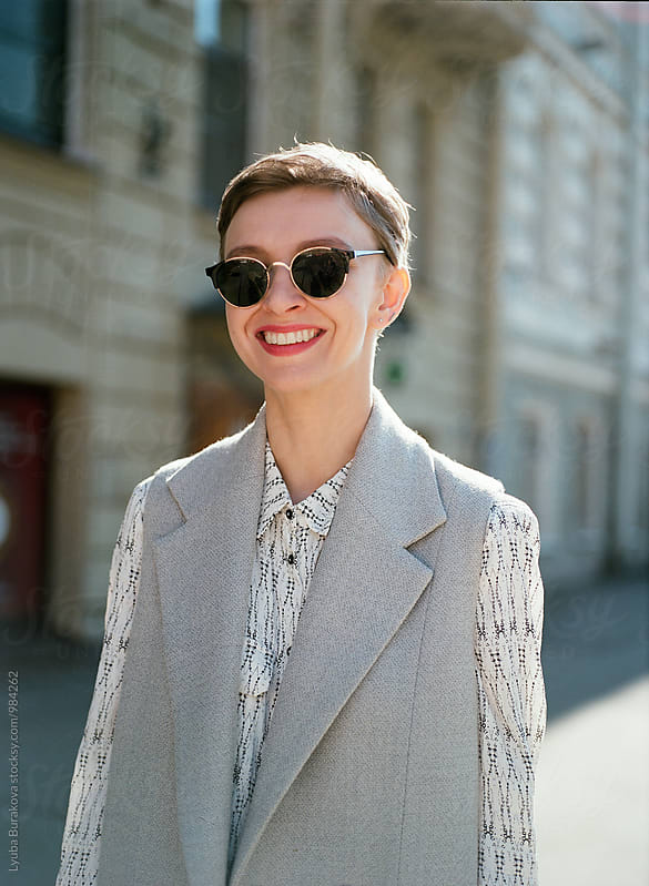 Smiling woman wearing sunglasses by Lyuba Burakova for Stocksy United
