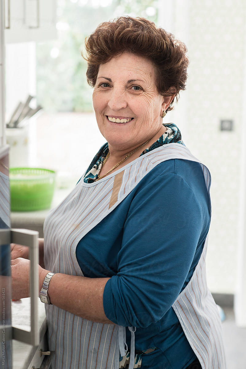 Mature spanish woman with an apron in the kitchen by Marta