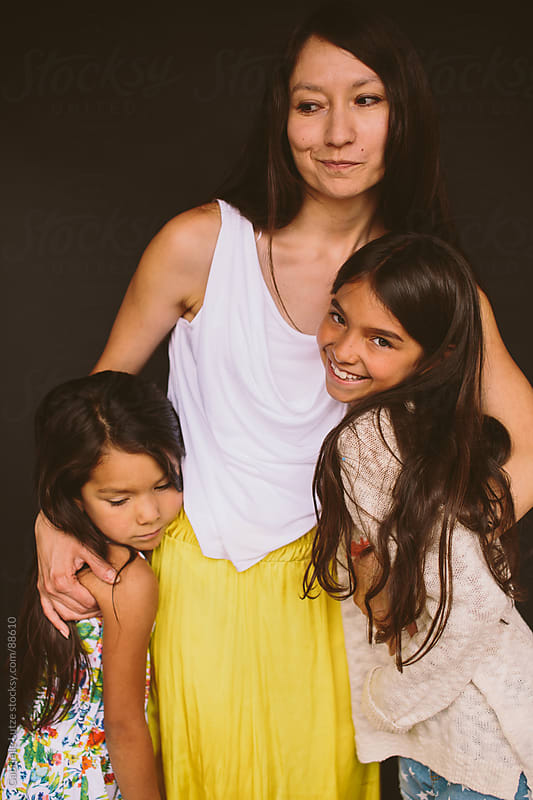 Mother and daughters hugging by Gabrielle Lutze for Stocksy United