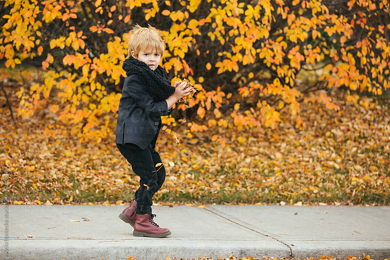 A young boy throwing leaves on a sidewalk by Ania Boniecka for Stocksy United