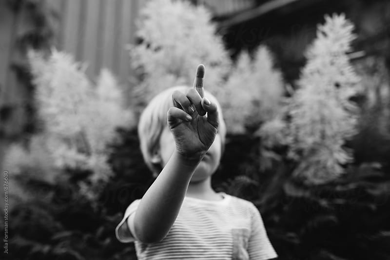 A child raises his hand to claim attention. by Julia Forsman for Stocksy United