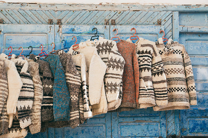 Hand knitted jumpers hanging against blue wooden panels, for sale at a market in Morocco by Maresa Smith for Stocksy United