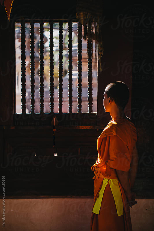 Young Buddhist monk looking out the window of the temple by michela ravasio for Stocksy United