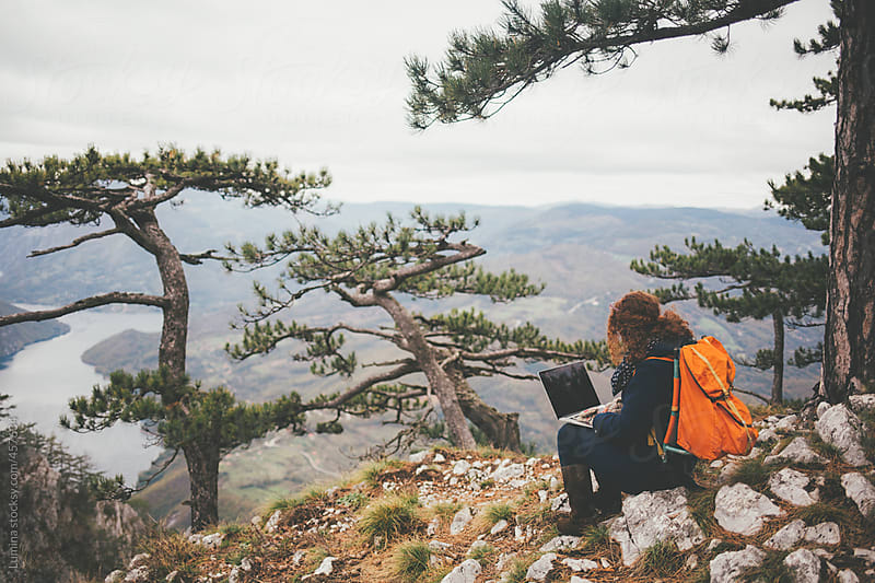 Woman With a Laptop Sitting on a Mountain's Edge by Lumina for Stocksy United