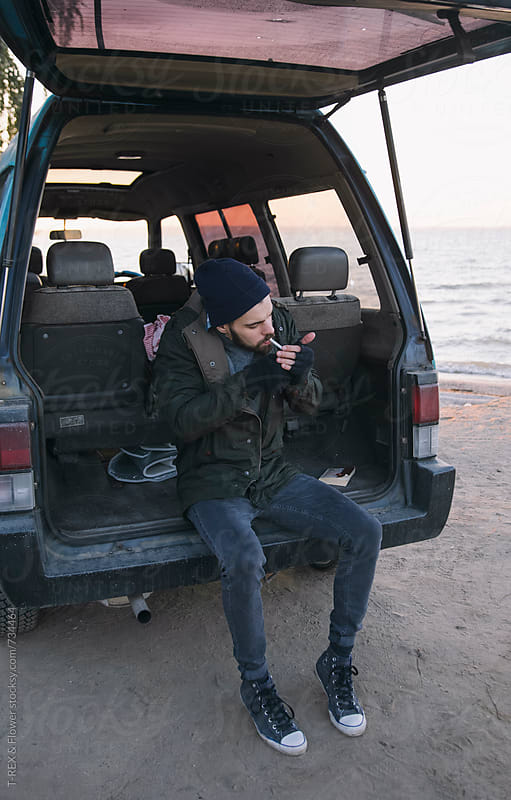 Man sitting in his minivan smoking by Danil Nevsky for Stocksy United