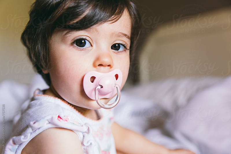 Cute baby girl sitting on a bed and looking at camera with her pacifier by Inuk Studio for Stocksy United