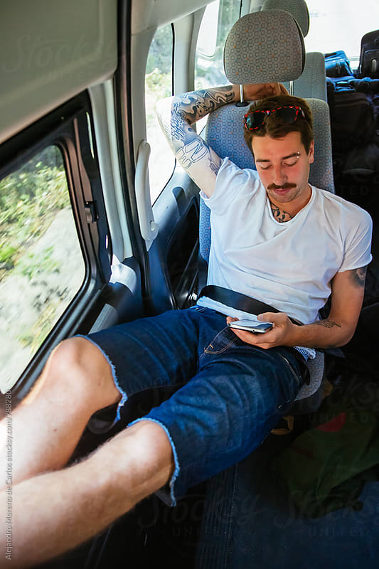 Young man checking his phone while traveling in a van by Alejandro Moreno de Carlos for Stocksy United