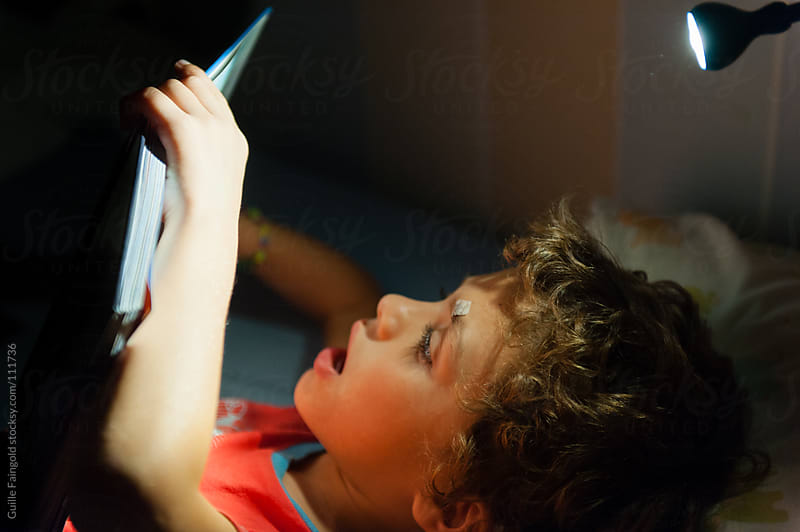 Child reading a book before going to sleep by Guille Faingold for Stocksy United