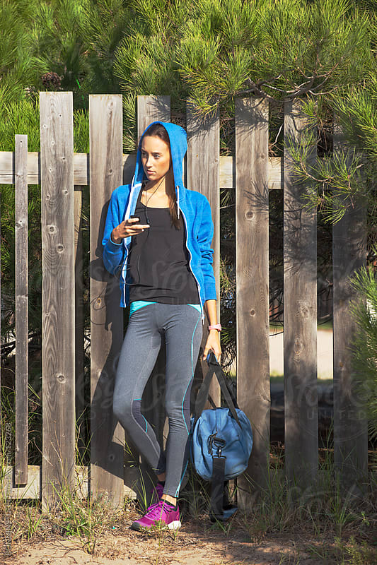 Young woman with blue sweatshirt resting on fence. Girl listening music with headphones. by BONNINSTUDIO for Stocksy United