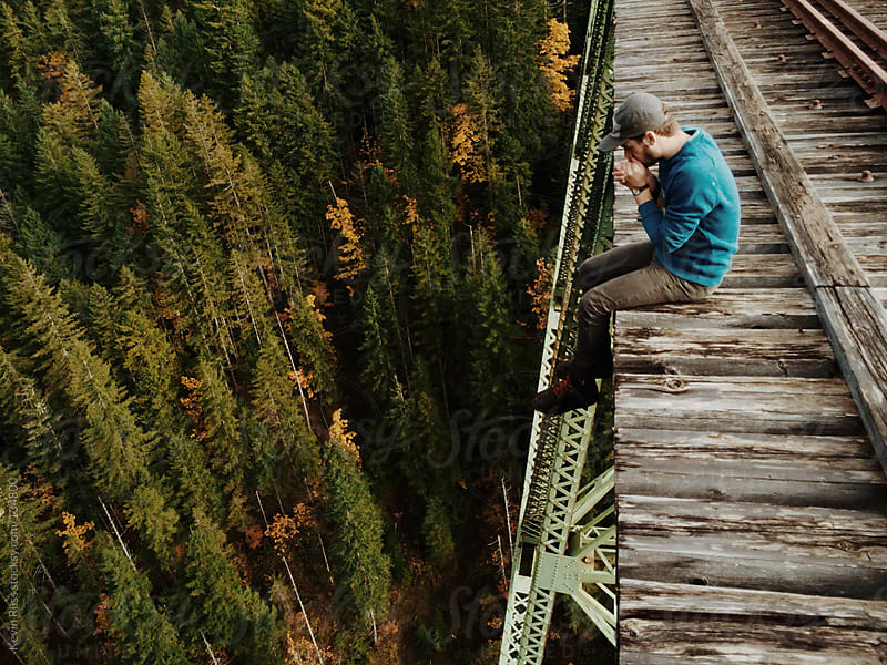 Man Sitting on Edge of Trestle by Kevin Russ for Stocksy United