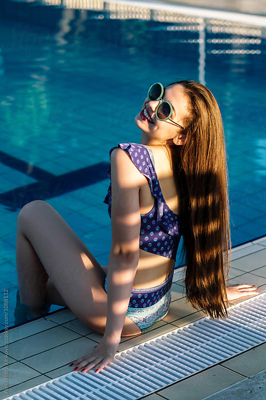 Beautiful Brunette Sitting by the Pool by Aleksandra Jankovic for Stocksy United