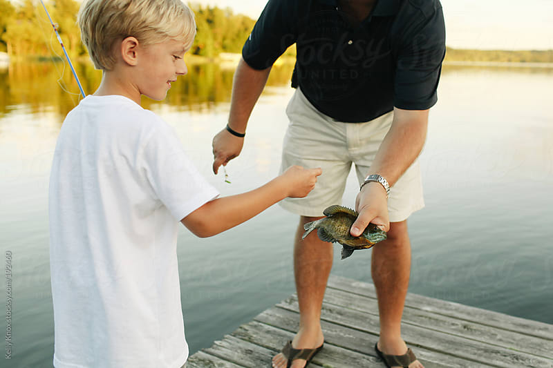 father and son have caught a fish by Kelly Knox for Stocksy United