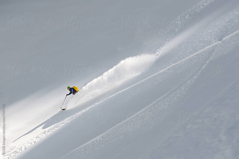 Skier making a turn splashing with snow in the sunlight by RG&B Images for Stocksy United