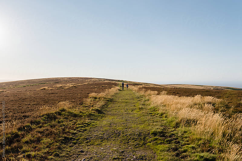 Taken from a distance Father and son walking up a hill by Rebecca Spencer for Stocksy United