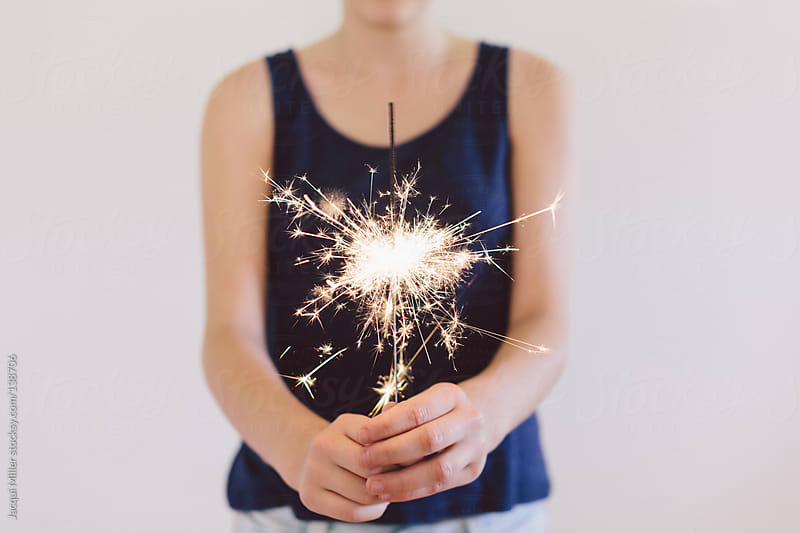 Teenage girl holds a sparkler in her hands. by Jacqui Miller for Stocksy United
