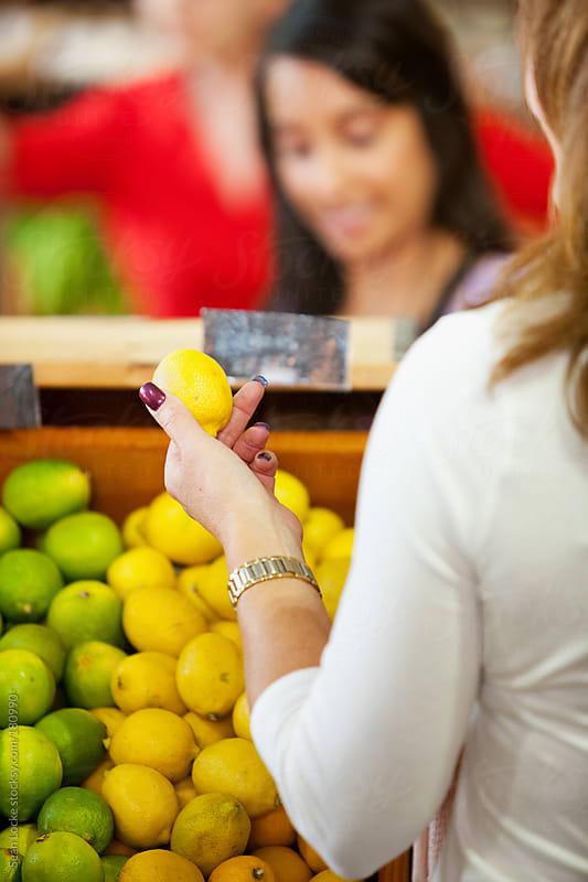 Market: Woman Holding Up Fresh Lemon by Sean Locke for Stocksy United