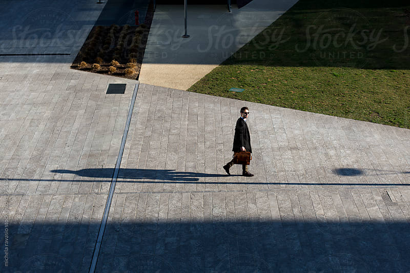 Young man walking with his briefcase out of the office building by michela ravasio for Stocksy United