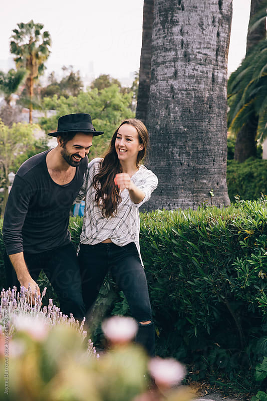 Young Couple Holding Hands and Walking in a LA Neighborhood. by Jayme Burrows for Stocksy United