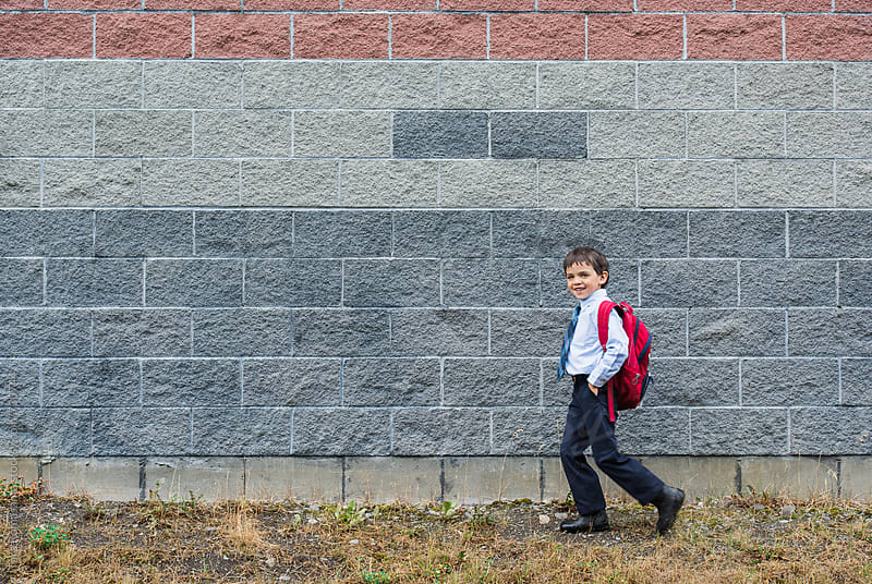 smiling young school boy with backpack walking to school by Tara Romasanta for Stocksy United