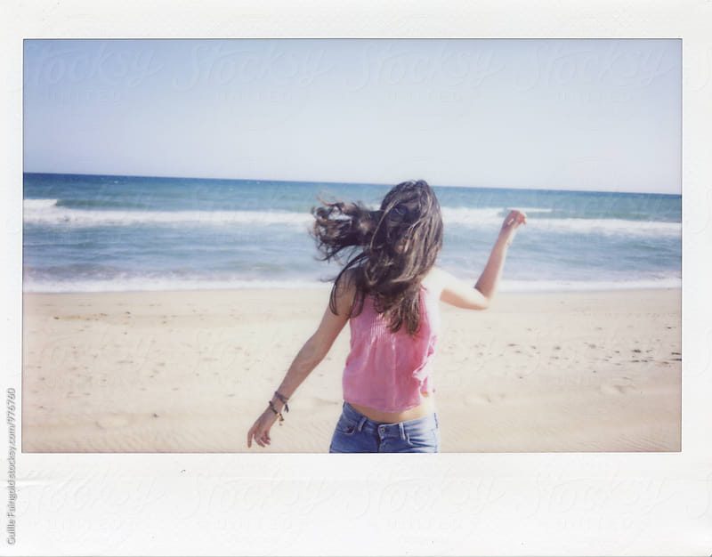 Instant shot of brunette with windy hair on beach by Guille Faingold for Stocksy United
