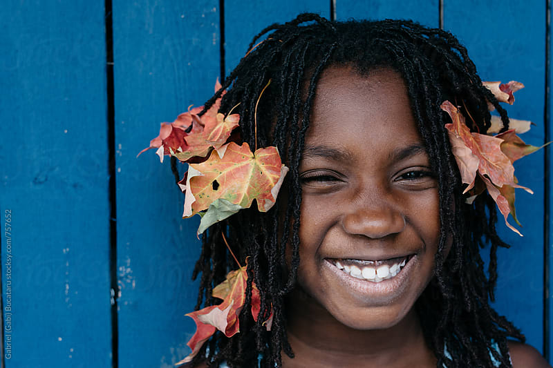 Smiling black girl with fall leaves in her hair by Gabriel (Gabi) Bucataru for Stocksy United