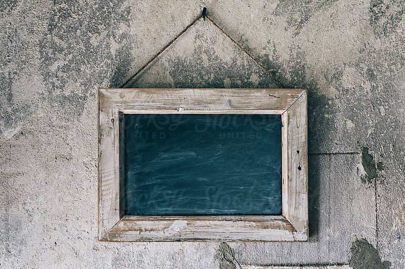Blackboard Hanging on an Old, Rustic Concrete Wall by Claudia Lommel for Stocksy United