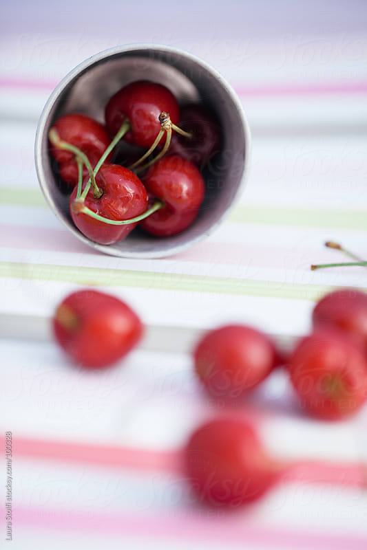 Red cherries in enamel tin on striped cloth by Laura Stolfi for Stocksy United