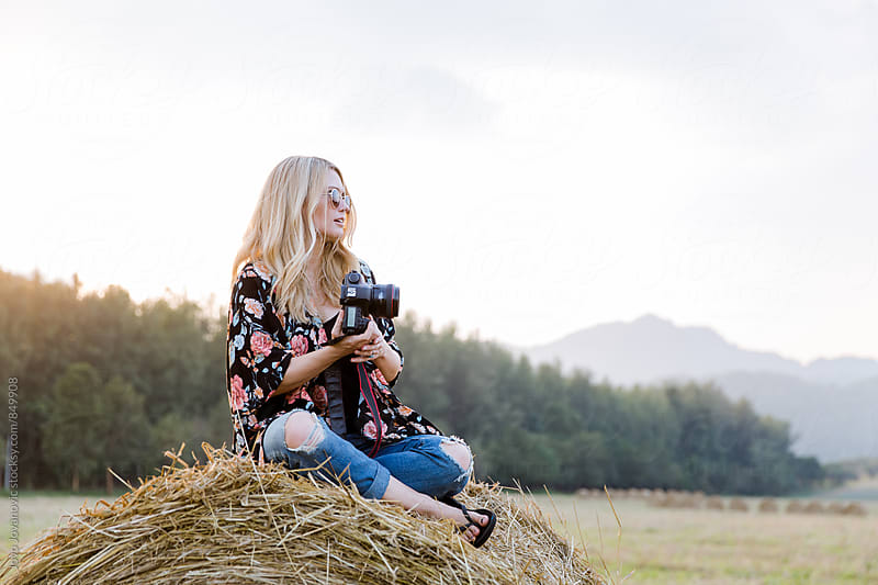 Stylish young photographer sitting on a straw bale in the countryside  by Jovo Jovanovic for Stocksy United